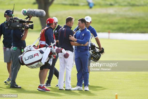 Rory McIlroy of Europe shakes hands with Justin Thomas of the United States on the 18th fairway during singles matches of the 2018 Ryder Cup at Le...
