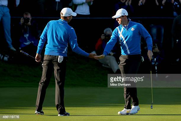 Rory McIlroy of Europe shakes hands with partner Sergio Garcia on the 1st green during the Morning Fourballs of the 2014 Ryder Cup on the PGA...