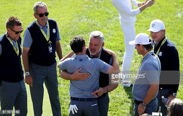 Rory McIlroy of Europe speaks to captain Darren Clarke and vicecaptains Sam Torrance Ian Poulter Padraig Harrington and Paul Lawrie on the first tee...