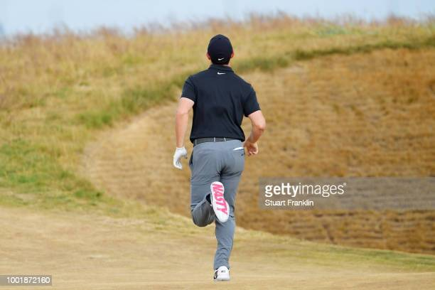 Rory McIlroy of Ireland runs ahead to view the hole during the first round of the 147th Open Championship at Carnoustie Golf Club on July 19 2018 in...