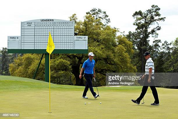 Rory McIlroy of Northern Ireland and Amateur Bradley Neil of Scotland walk across a green during a practice round prior to the start of the 2015...
