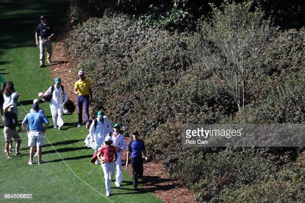 Rory McIlroy of Northern Ireland and amatuer Toto Gana of Chile walk to the sixth green during a practice round prior to the start of the 2017...
