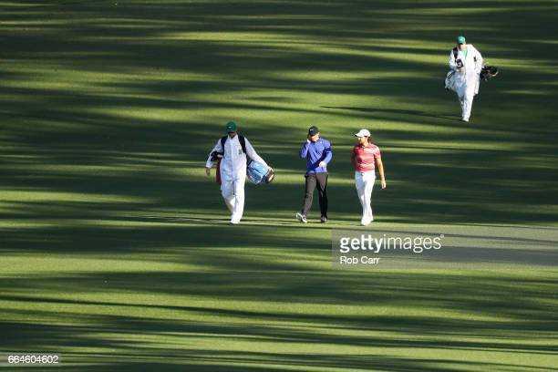 Rory McIlroy of Northern Ireland and amatuer Toto Gana of Chile walk down the second fairway during a practice round prior to the start of the 2017...