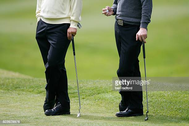 Rory McIlroy of Northern Ireland and Ben Curtis of USA wait to take their turn putting during the first round of the BMW PGA Golf Championship at the...