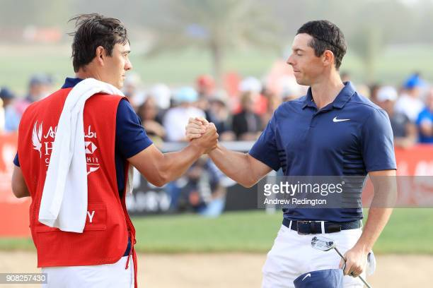 Rory McIlroy of Northern Ireland and caddie Harry Diamond shake hands after finishing on the 18th green during the final round of the Abu Dhabi HSBC...