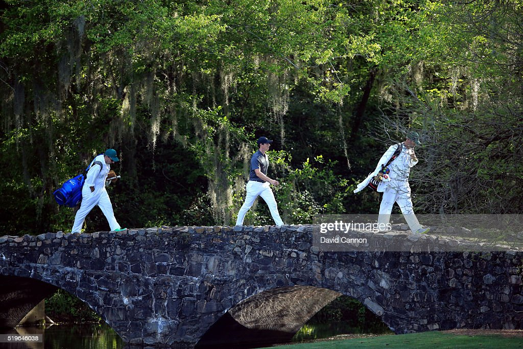 Rory McIlroy of Northern Ireland and caddie J.P. Fitzgerald walk across the Nelson bridge from the 12th green to the 13th tee during the first round of the 2016 Masters Tournament at Augusta National Golf Club on April 7, 2016 in Augusta, Georgia.