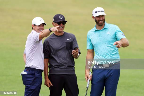 Rory McIlroy of Northern Ireland and Dustin Johnson of the United States laugh with coach Claude Harmon III during a practice round prior to the...
