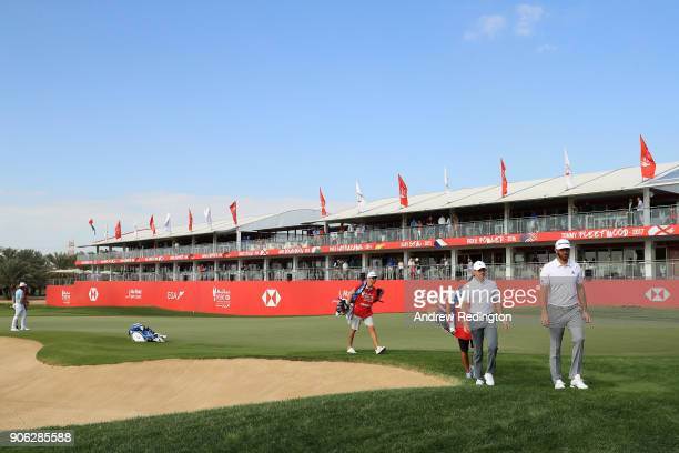Rory McIlroy of Northern Ireland and Dustin Johnson of the United States walk from the 18th green during round one of the Abu Dhabi HSBC Golf...