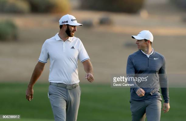 Rory McIlroy of Northern Ireland and Dustin Johnson of the United States walk down the fairway on the par 5 10th hole during the first round of the...
