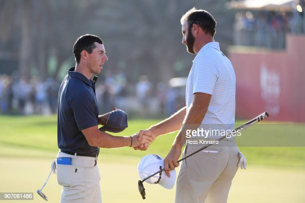 Rory McIlroy of Northern Ireland and Dustin Johnson of the United States shake hands on the 18th green during round two of the Abu Dhabi HSBC Golf...