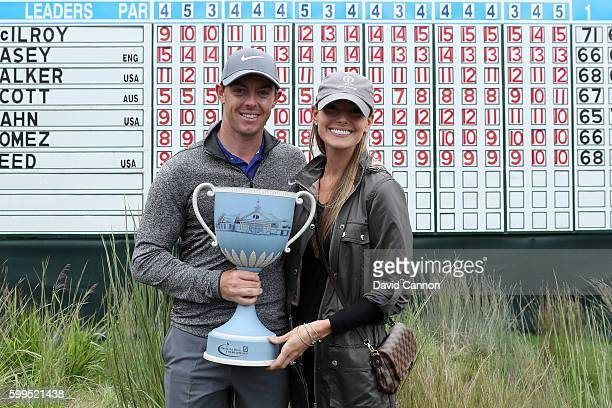Rory McIlroy of Northern Ireland and fiancee Erica Stoll pose with the trophy during the final round of the Deutsche Bank Championship at TPC Boston...