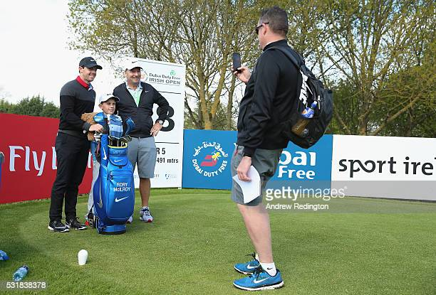 Rory McIlroy of Northern Ireland and his caddie JP Fitzgerald have their picture taken with a young fan on the 18th hole during practice for the...