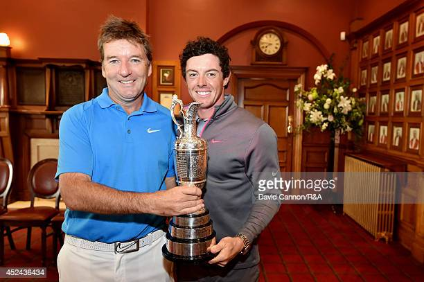 Rory McIlroy of Northern Ireland and his caddie JP Fitzgerald pose with the Claret Jug in the clubhouse after his twostroke victory in The 143rd Open...