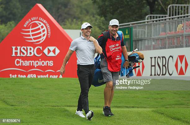 Rory McIlroy of Northern Ireland and his caddie JP Fitzgerald walk together on the first hole during the Pro Am prior to the start of the WGC HSBC...