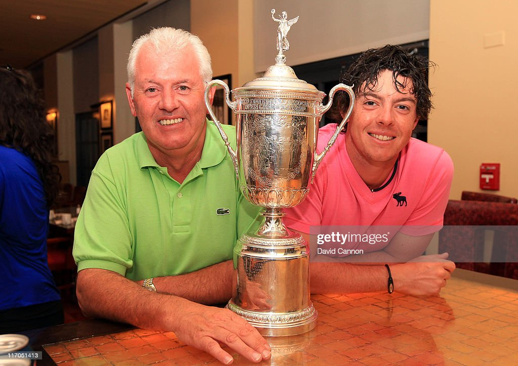 Rory McIlroy of Northern Ireland and his father Gerry McIlroy pose with the trophy after his eight-stroke victory during the 111th U.S. Open at Congressional Country Club on June 19, 2011 in Bethesda, Maryland.