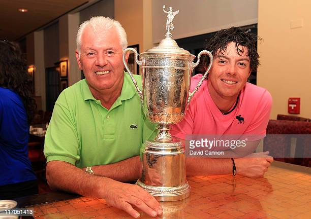 Rory McIlroy of Northern Ireland and his father Gerry McIlroy pose with the trophy after his eightstroke victory during the 111th US Open at...