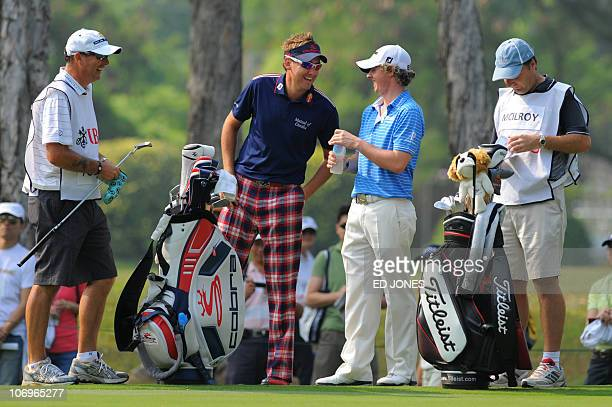 Rory McIlroy of Northern Ireland and Ian Poulter of England celebrate their respective plays on the ninth hole during the Hong Kong Open golf...