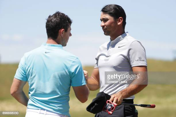 Rory McIlroy of Northern Ireland and Jason Day of Australia shake hands after finishing on the ninth green during the second round of the 2017 US...