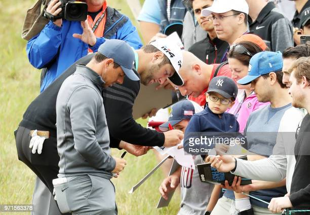 Rory McIlroy of Northern Ireland and Jon Rahm of Spain sign autographs during practice rounds prior to the 2018 US Open at Shinnecock Hills Golf Club...