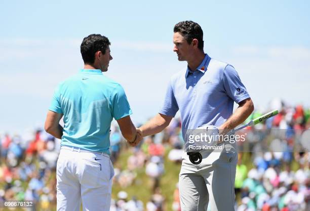 Rory McIlroy of Northern Ireland and Justin Rose of England shake hands after finishing on the ninth green during the second round of the 2017 US...