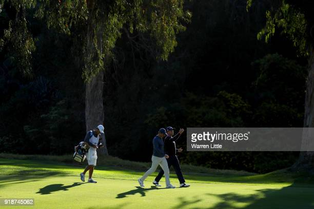 Rory McIlroy of Northern Ireland and Justin Thomas walk across the 13th hole during the first round of the Genesis Open at Riviera Country Club on...