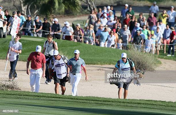 Rory McIlroy of Northern Ireland and Marc Warren of Scotland walk with their caddies during the third round of the 2015 Omega Dubai Desert Classic on...