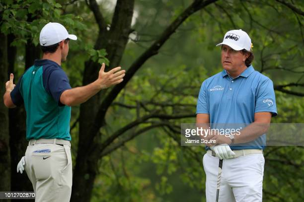 Rory McIlroy of Northern Ireland and Phil Mickelson of the United States talk on the second tee during a practice round prior to the 2018 PGA...