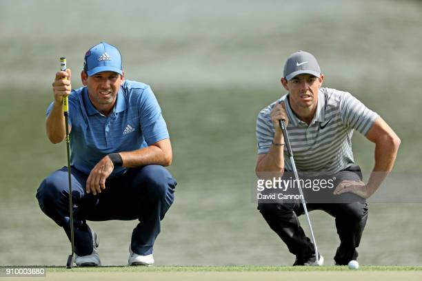 Rory McIlroy of Northern Ireland and Sergio Garcia of Spain line up their putts on the par 4 ninth hole during the first round of the Omega Dubai...