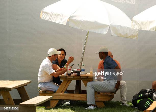 Rory McIlroy of Northern Ireland and Tiger Woods of the United States sit at a picnic table to eat lunch after their third round of The Northern...