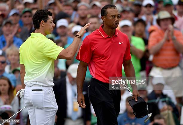 Rory McIlroy of Northern Ireland and Tiger Woods of the United States shake hands on the 18th green during the final round of the 2015 Masters at...