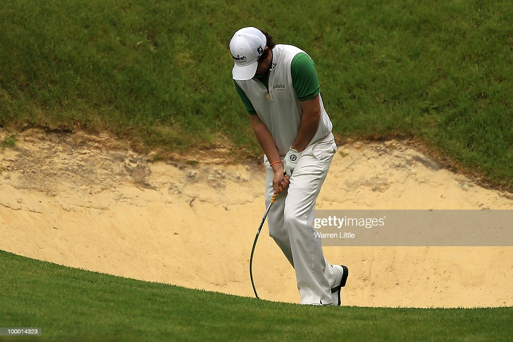 Rory McIlroy of Northern Ireland bends his sand wedge after failing to hit out of a greenside bunker on the 10th hole during the first round of the BMW PGA Championship on the West Course at Wentworth on May 20, 2010 in Virginia Water, England.