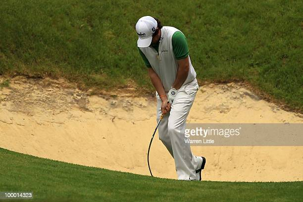 Rory McIlroy of Northern Ireland bends his sand wedge after failing to hit out of a greenside bunker on the 10th hole during the first round of the...