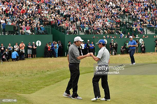 Rory McIlroy of Northern Ireland bumps fists with his caddie JP Fitzgerald after his eagle on the 18th hole during the third round of The 143rd Open...