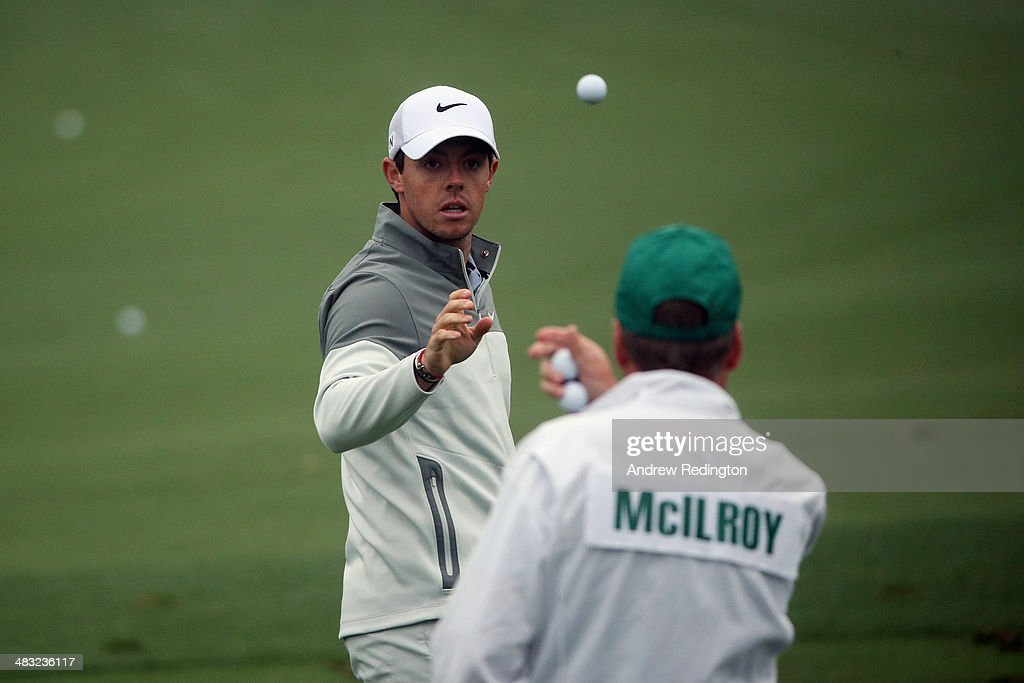 Rory McIlroy of Northern Ireland catches a golf ball from caddie J.P. Fitzgerald during a practice round prior to the start of the 2014 Masters Tournament at Augusta National Golf Club on April 7, 2014 in Augusta, Georgia.