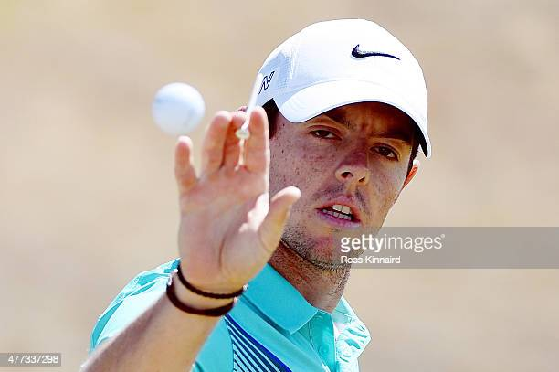Rory McIlroy of Northern Ireland catches a golf ball on the practice range during a practice round prior to the start of the 115th U.S. Open...