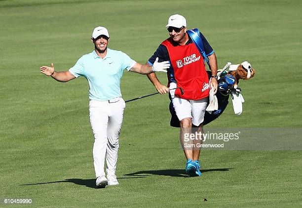 Rory McIlroy of Northern Ireland celebrates alongside his caddie JP Fitzgerald after holing a shot for eagle on the 16th hole during the final round...