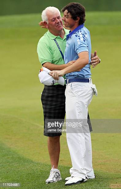 Rory McIlroy of Northern Ireland celebrates his eightstroke victory with his father Gerry McIlroy on the 18th green during the 111th US Open at...