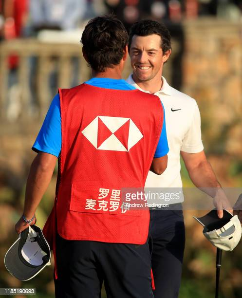 Rory McIlroy of Northern Ireland celebrates his victory in a playoff on the 18th green with his caddie Harry Diamond during Day Four of the WGC HSBC...
