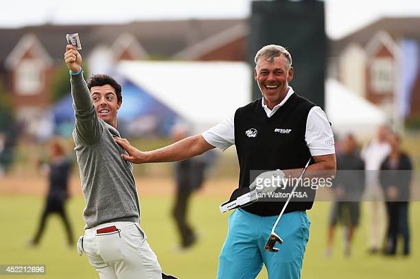 Rory McIlroy of Northern Ireland celebrates winning a bet against Darren Clarke of Northern Ireland after their practice round prior to the start of...