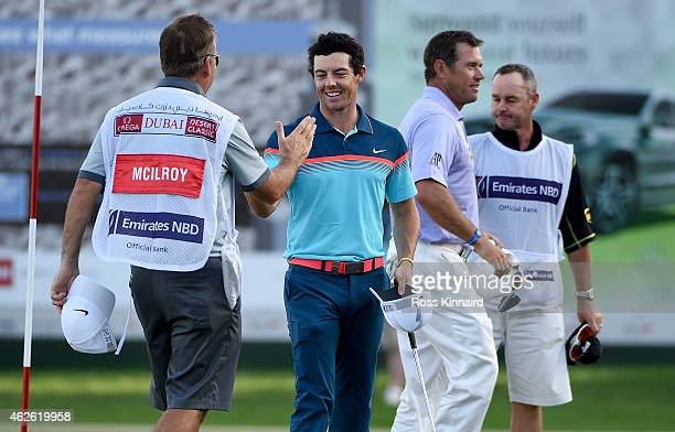 Rory McIlroy of Northern Ireland celebrates with his caddie J P Fitzgerald on the 18th green the final round of the Omega Dubai Desert Classic at the...