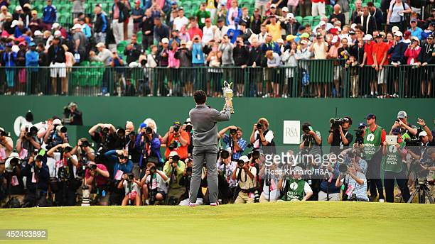 Rory McIlroy of Northern Ireland celebrates with the Claret Jug after his twostroke victory on the 18th green as photographers look on during the...