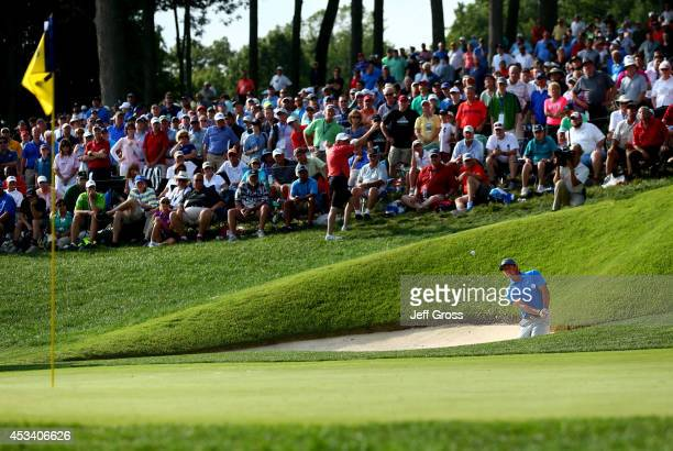 Rory McIlroy of Northern Ireland chips from a bunker to the 14th green during the third round of the 96th PGA Championship at Valhalla Golf Club on...