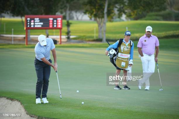 Rory McIlroy of Northern Ireland chips onto 13th green over the ball of Lee Westwood of England who is watching on during Day 2 of the Abu Dhabi HSBC...