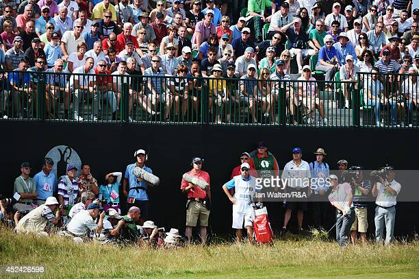 Rory McIlroy of Northern Ireland chips to the fifth green as media and a grandstand of patrons look on during the final round of The 143rd Open...