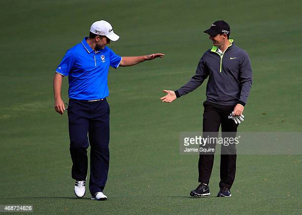 Rory McIlroy of Northern Ireland congratulates Amateur Bradley Neil of Scotland after Neil chipped in from the fairway during a practice round prior...