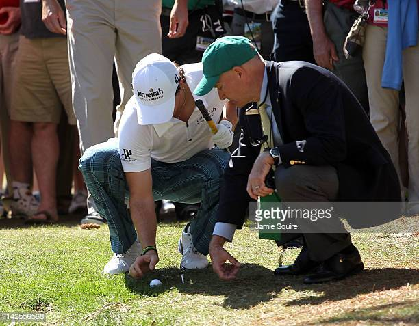 Rory McIlroy of Northern Ireland examines his ball placement with a rules official during the third round of the 2012 Masters Tournament at Augusta...