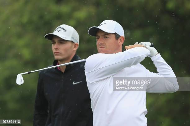 Rory McIlroy of Northern Ireland hit a shot as Aaron Wise of the United States looks on during a practice round prior to the 2018 US Open at...