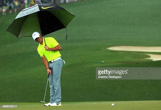 Rory McIlroy of Northern Ireland hits a putt in the rain during a practice round prior to the start of the 2015 Masters Tournament at Augusta...
