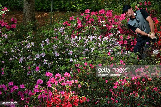 Rory McIlroy of Northern Ireland hits a shot out of the the azaleas bushes behind the 13th green during the second round of the 2014 Masters...
