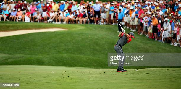 Rory McIlroy of Northern Ireland hits an approach on the first hole during the first round of the 96th PGA Championship at Valhalla Golf Club on...